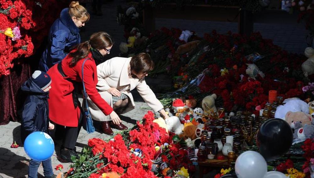 La gente se acerca a poner flores a las víctimas del accidente