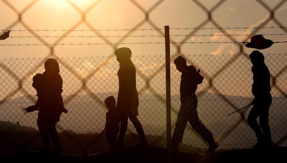 Inmigrantes caminan alrededor de una valle cerca del campo de refugiados de Idomeni
