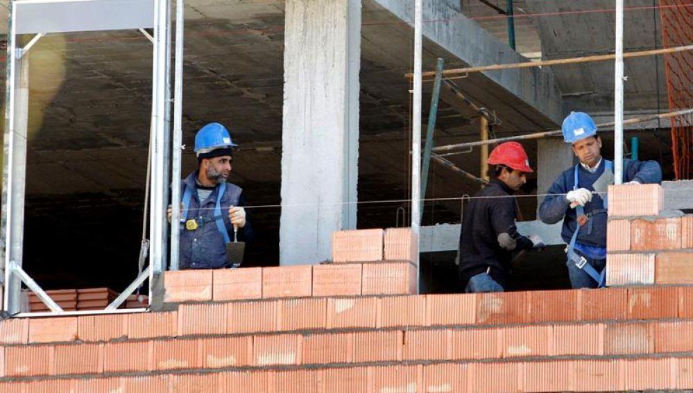 Tres obreros trabajan en la construcción de una vivienda
