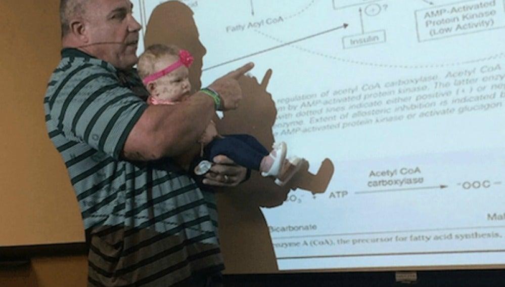 El profesor sosteniendo a la bebé