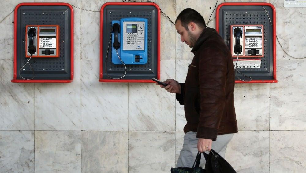 Un peatón camina mirando su teléfono móvil