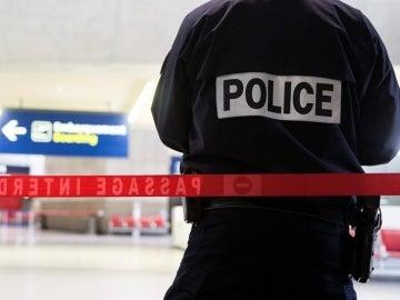 Un agente de policía vigila una zona acordonada en el interior del aeropuerto Charles de Gaulle de París, Francia