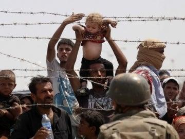 Varios refugiados aguardan en la frontera
