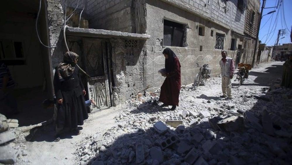Varias personas inspeccionan edificios en ruinas tras los bombardeos en el pueblo de Deir al Asafi, al sureste de Damasco (Siria)