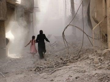 Una mujer y su hija caminan entre las ruinas en SiriaUna mujer y su hija caminan entre las ruinas en Siria