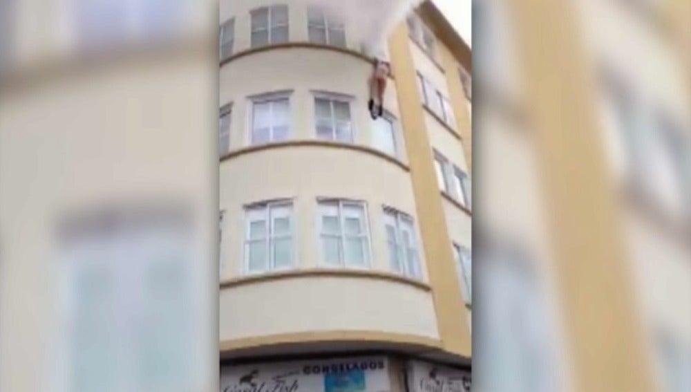 Una mujer salta por la ventana para huir de un incendio y la recogen con una manta