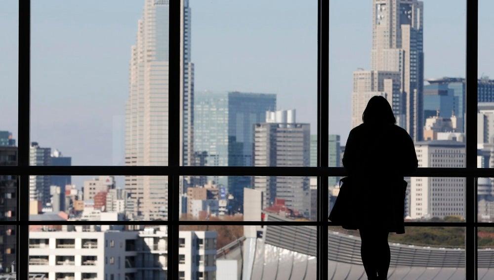 Contorno de una mujer mirando por la ventana
