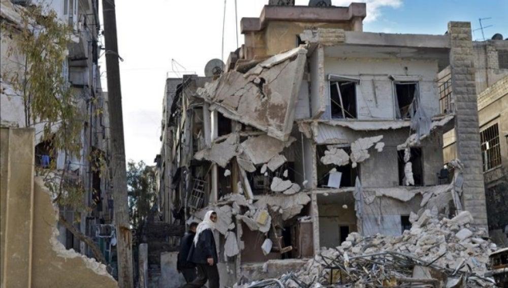 Varios civiles pasando por un edificio destruído por los bombardeos en Alepo
