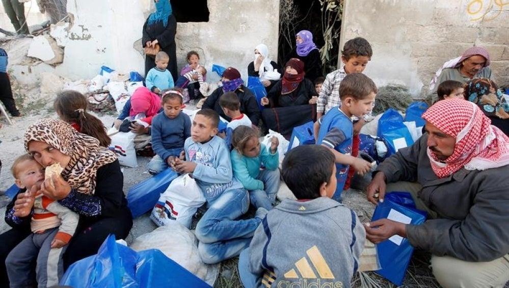 Familias sirias esperan la entrega de ayuda humanitaria