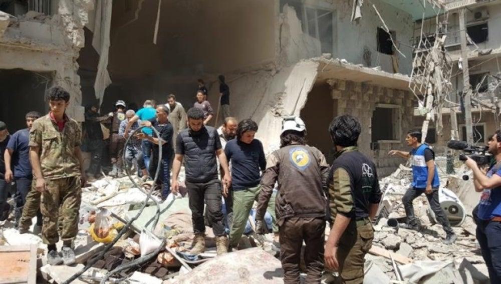 Sirios en el lugar de los ataques aéreos en el barrio Bustan Al Qasr