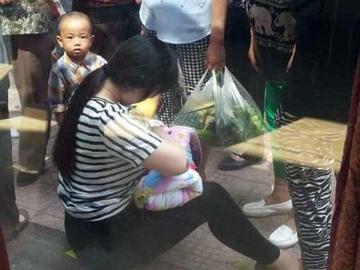 La mujer amamanta al pequeño en la calle
