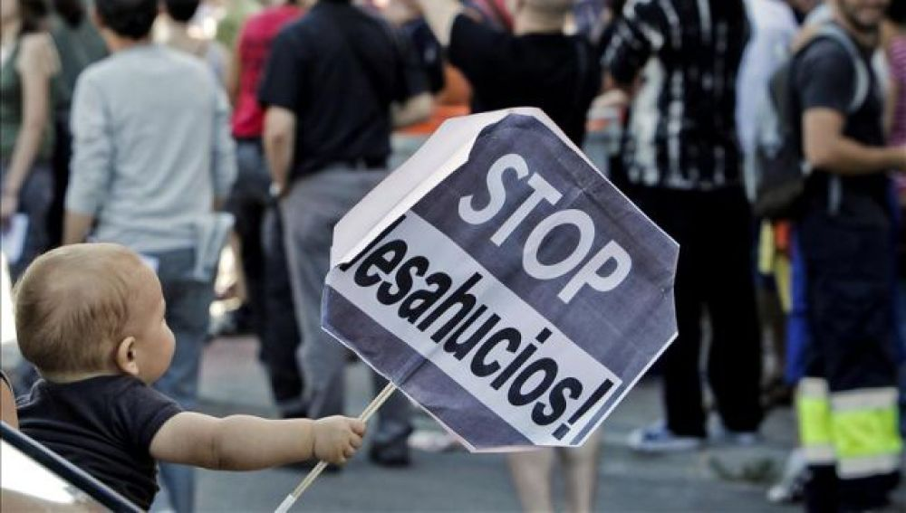 Un niño sostiene un cartel de Stop desahucios (Archivo)