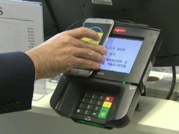 Un hombre paga en un datáfono con su 'smartphone'.