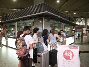 Viajeros hacen cola en el punto de información de Atocha durante la primera jornada de huelga de Renfe