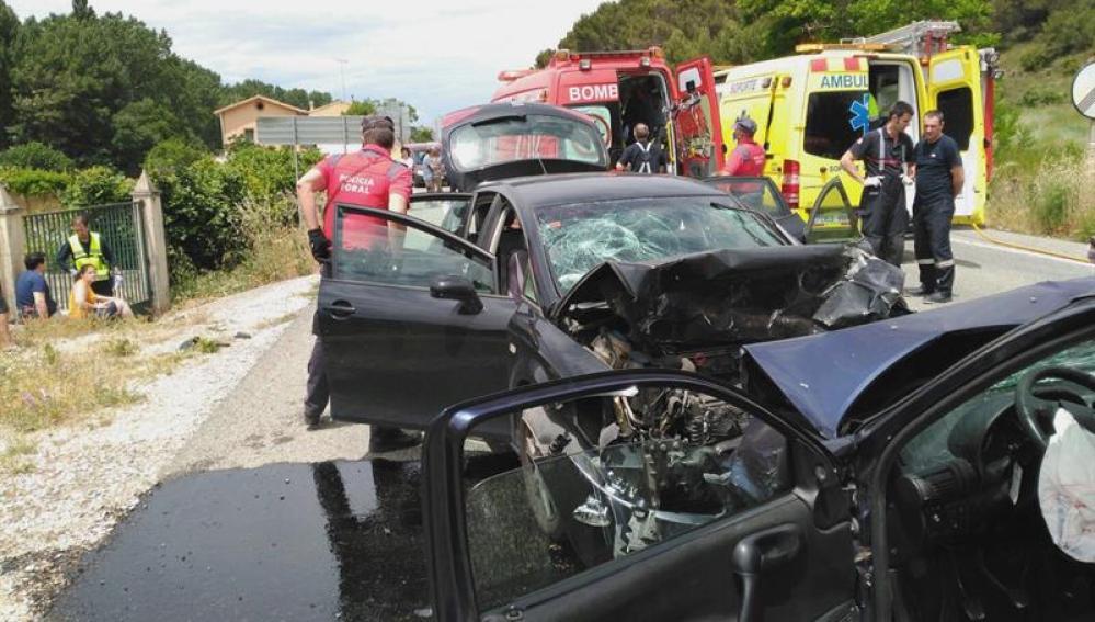 Agentes de la Policía Foral y miembros del cuerpo de Bomberos de Navarra trabajan en un accidente en la N121 este domingo.