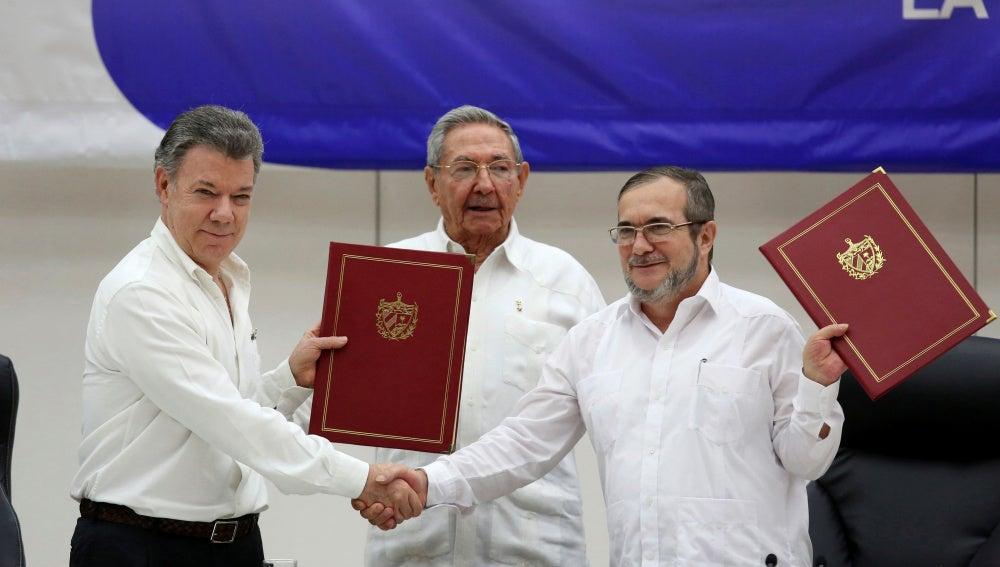 El presidente de Colombia, Juan Manuel Santos, y el líder de las FARC, Rodrigo Londoño 'Timochenko', ante Raúl Castro
