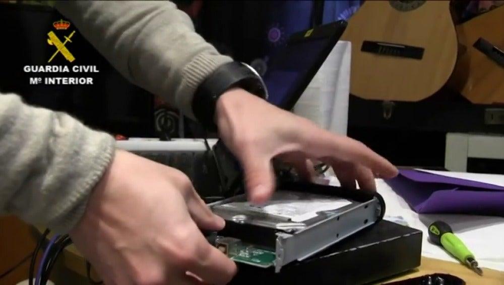 Un guardia civil manipulando una memoria informática (Archivo)