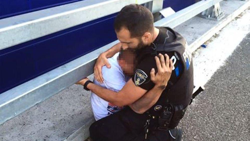 El agente abraza al chico tras el rescate.