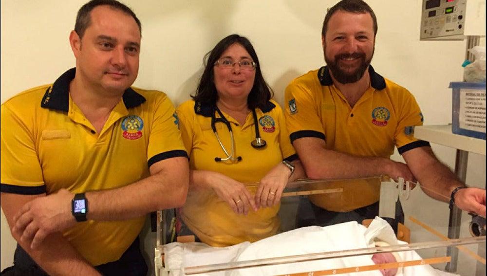 El equipo de sanitarios que atendió a la joven posa con el bebé.