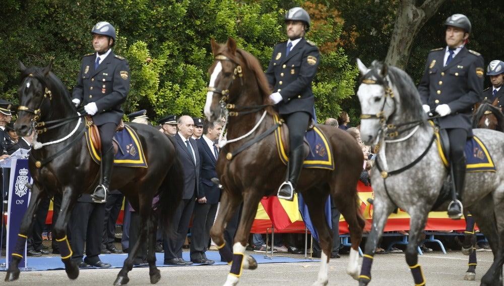 El ministro del Interior, Jorge Fernández Díaz (c, detrás), preside un desfile durante el homenaje que la Policía Nacional ha rendido a la Fiesta Nacional