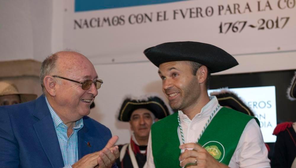 Iniesta es aplaudido por el alcalde de Carboneros (Jaén), Domingo Bonillo, tras entregarle el sombrero de tres picos de Carlos III