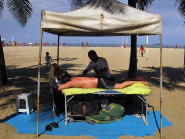 Un hombre da un masaje en la playa