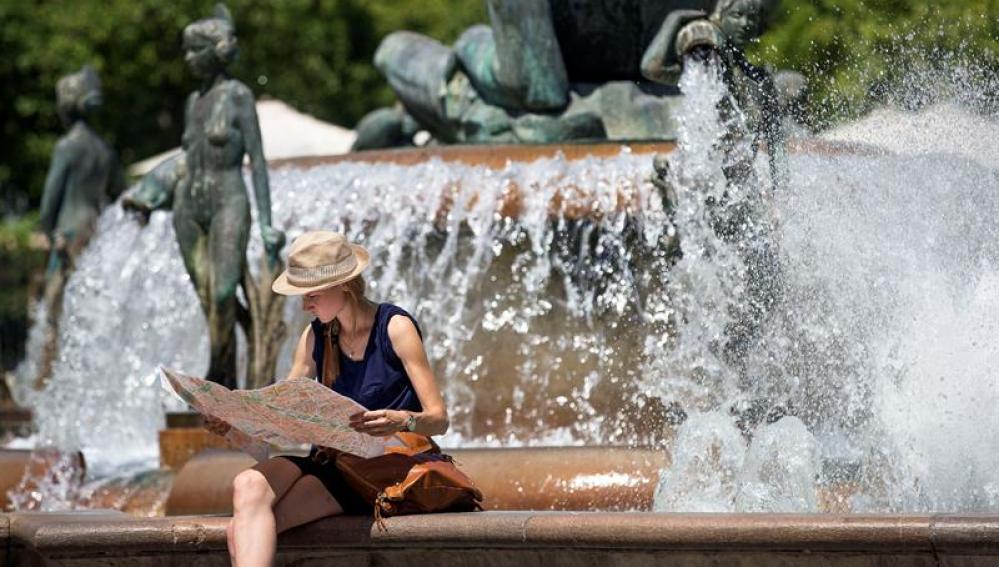 Una turista junto a una fuente