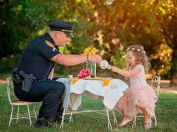 La pequeña de dos años toma el té con el Policía que le salvó la vida.
