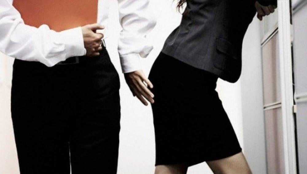 Un hombre tocándole el culo a una mujer en el trabajo