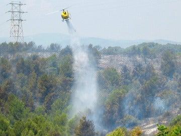 Un helicóptero remoja la zona afectada por un incendio forestal en un area boscosa en Segur de Calafellen (Tarragona)