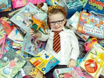 Nathan sonríe junto a los juguetes que ha comprado para donarlos a una asociación.