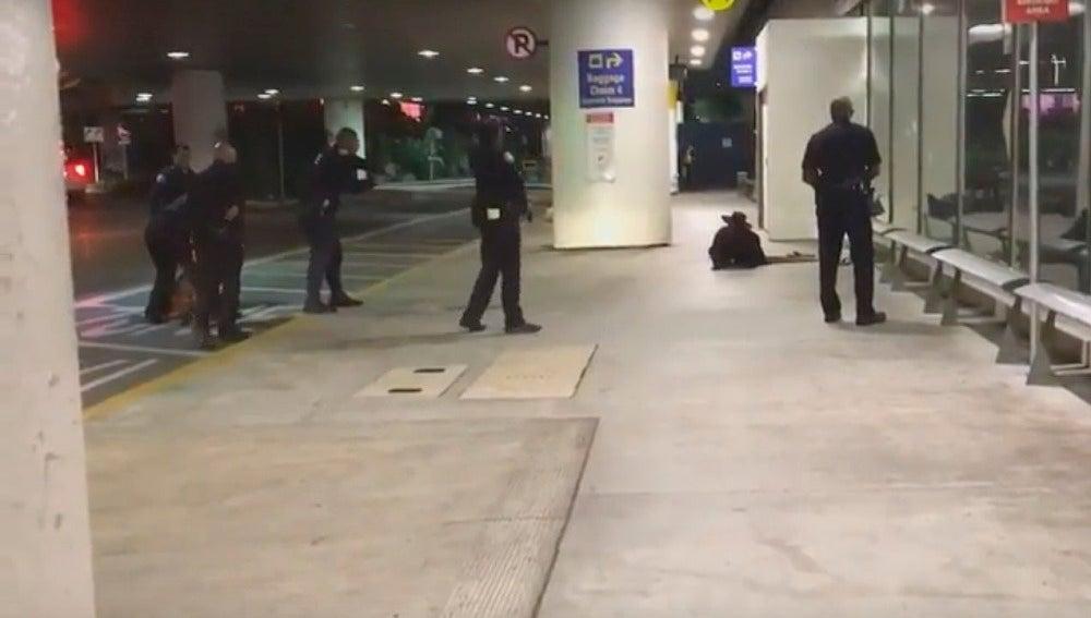 Momento en que los agentes inmovilizan al sujeto en el aeropuerto de Los Ángeles.
