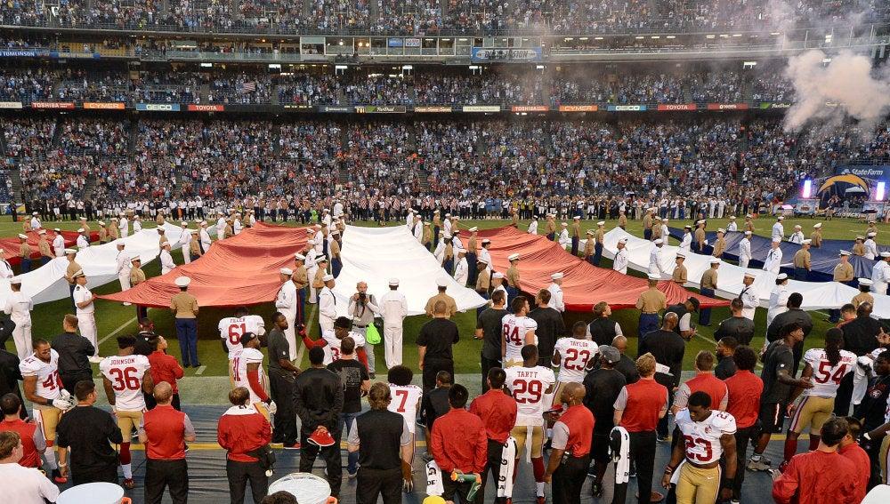 Colin Kaepernick, en la parte inferior de la fotografía (lleva el dorsal 7), de rodillas mientras suena el himno de Estados Unidos