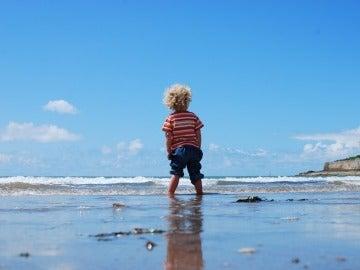 Un niño pequeño pasea en por la playa