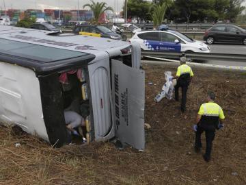 Efectivos de la Guardia Urbana inspeccionan el autobús volcado