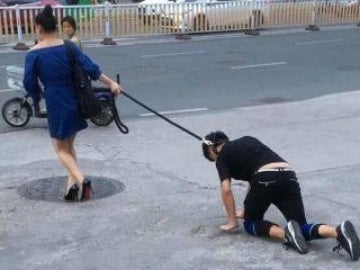 Una mujer china pasea a su novio con una correa como si fuera un perro