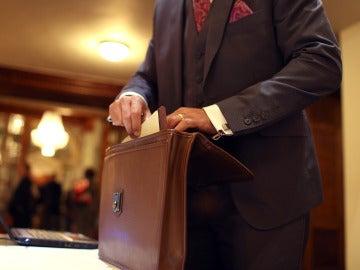 Un hombre sacando documentos de un maletín