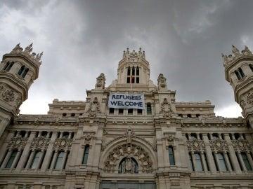 """Detalle de una pancarta con la leyenda """"Refugees Welcome"""" -""""Refugiados, bienvenidos"""", colocada en la fachada del Palacio de Cibeles"""