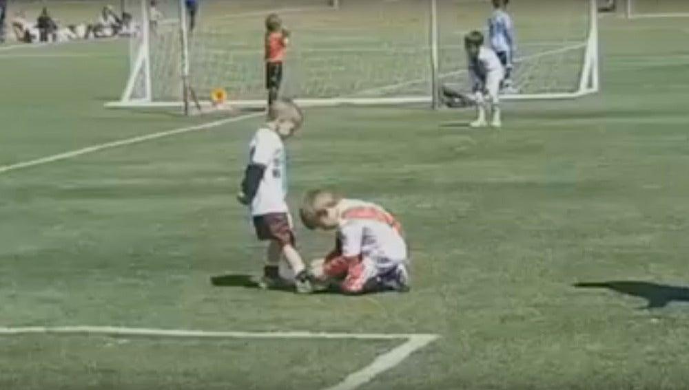 Un niño ayuda a otro a atarse la bota durante un partido en Argentina