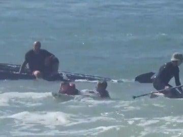 Frame 35.668204 de: Unos surfistas rescatan a dos niños después de volcar el barco donde viajaban