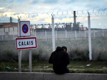 Un joven permanece sentado frente a una verja en del campamento de inmigrantes situado en Calais