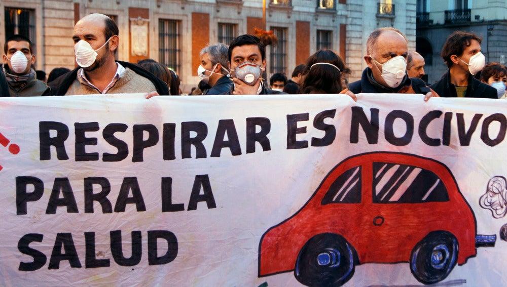 La gente usa máscaras y sostienen una pancarta durante un flashmob para marcar el problema de la contaminación en el centro de Madrid