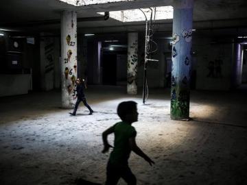 Niños sirios corren por los pasillos de una escuela