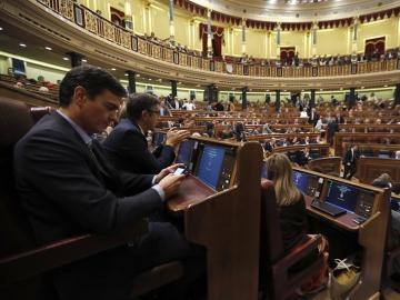 Pedro Sánchez mirando su móvil en la segunda  jornada del debate de investidura