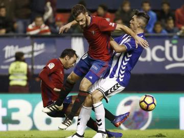 Miguel de las Cuevas y Roberto Torres, del Osasuna, intentan arrebatar el esférico al centrocampista del Deportivo Alavés, Víctor Camarasa.