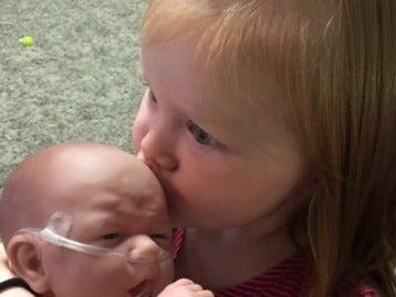 Una niña con el muñeco que imita a su hermano enfermo