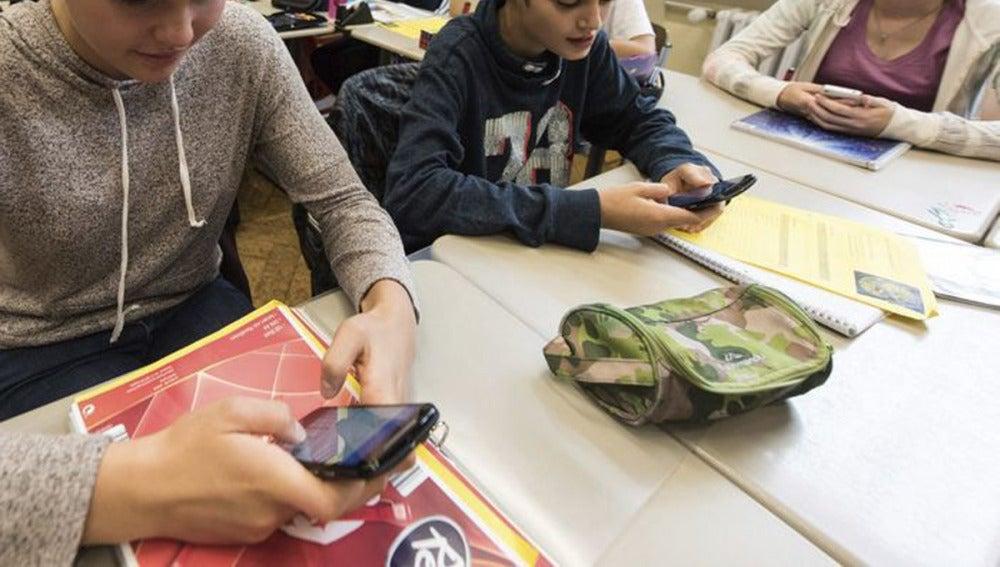 Unos alumnos utilizan el smartphone en clase