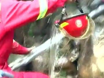 Frame 14.166989 de: Bomberos peruanos utilizan sus cascos para transportar el agua en la lucha contra las llamas