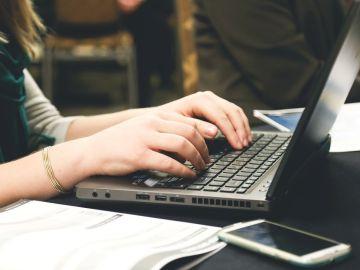Alumna escribiendo en un portátil