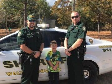 Niño y dos agentes de sheriff